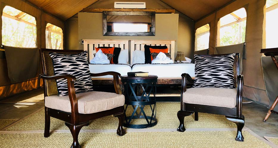 Two single beds and sitting chairs with zebra-pattern throw pillows under a tent at a luxury African safari camp.