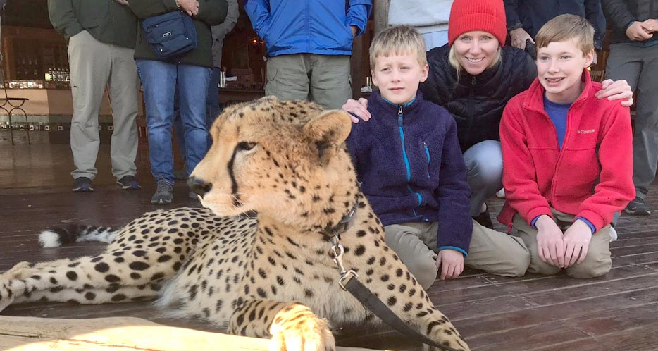 A mother and sons pose with a tame cheetah.