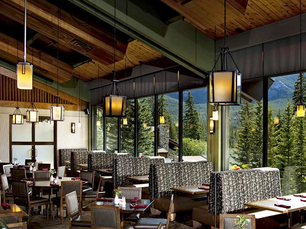 Dining area with a view on pine trees at the Banff Park Lodge