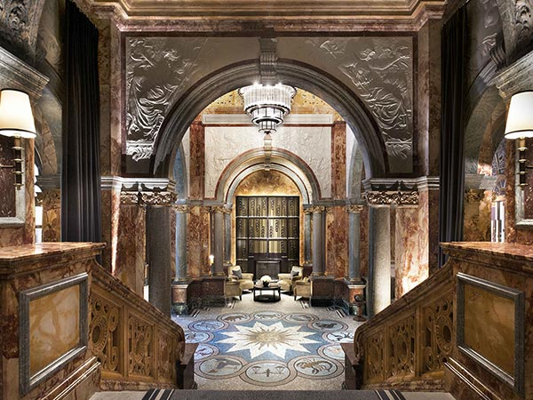 The Kimpton Fitzroy London lobby features a grand stone arch and chandelier overhead, with mosaic tiling on the floor.