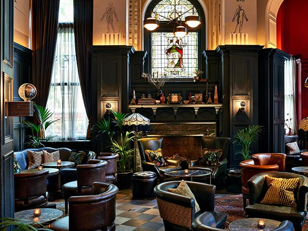 Dark leather chairs and a smoldering fireplace characterize the lounge area of the Kimpton Fitzroy London.
